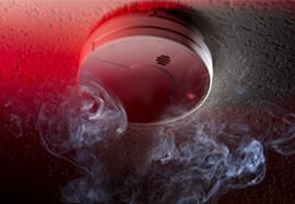 Smoke alarm on the wall detecting smoke and carbon monoxide